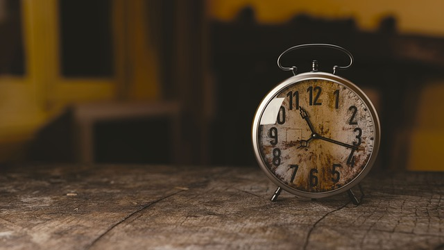 Round table clock on the right side on a wooden table. Setting a routine, can help maintain good sleep.