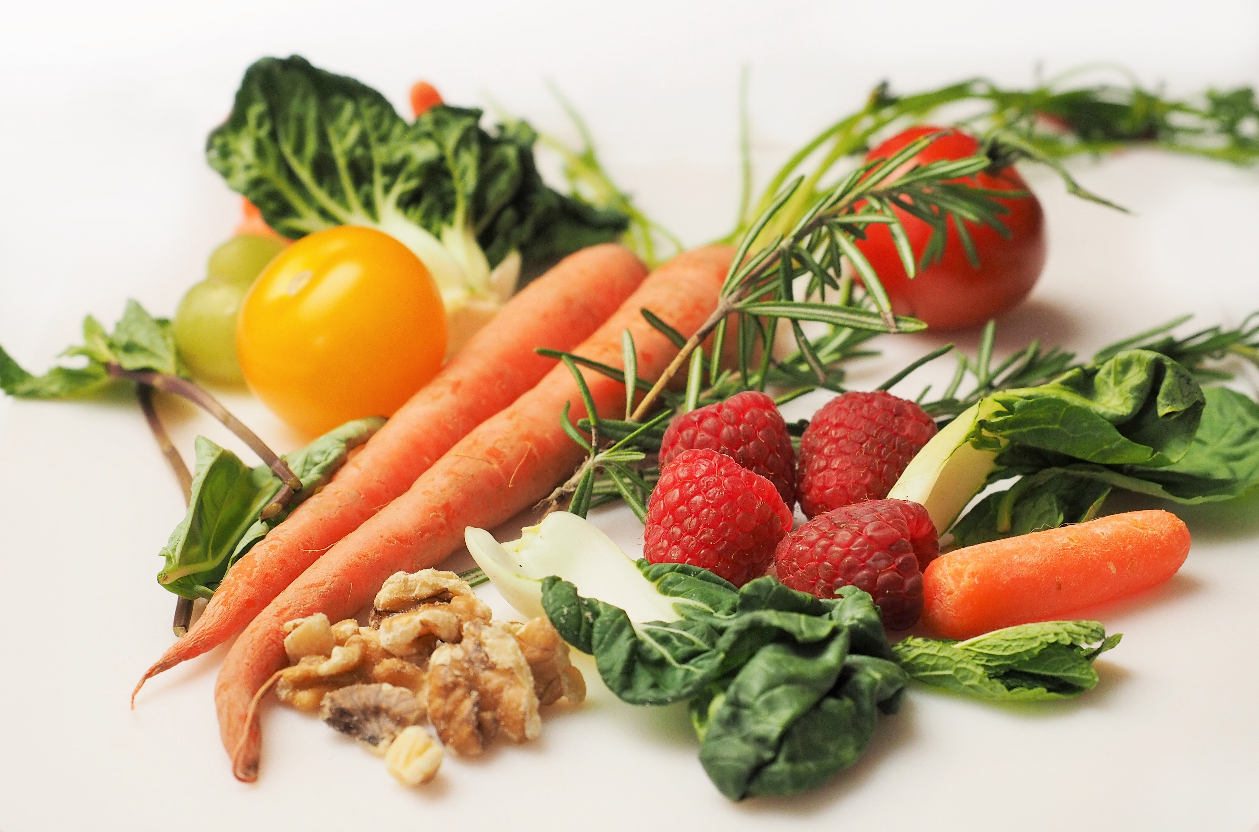 A photo of fresh carrots, lettuce, nuts, herbs, tomatoes and raspberries. Diet is essential for a good sleep.